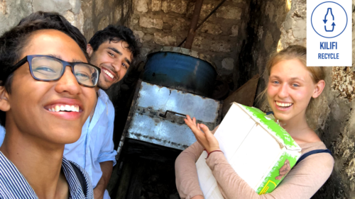 Team members smiling at a camera in front of the kiln in storage